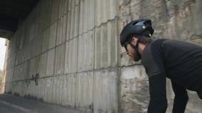 在戴黑成套装备、盔甲和太阳镜的马鞍外面的年轻人适合的男性骑自行车者骑马自行车 r 股票视频