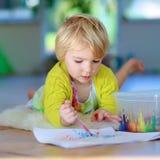 在户内地板上的小女孩图画 库存照片