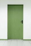 在户内干净的墙壁上的一个木门 免版税图库摄影