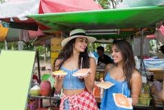在户外咖啡馆走的街道的两妇女游人购买新鲜水果在亚洲城市愉快的微笑的可爱的女孩  免版税图库摄影