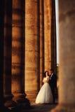 在户外婚礼礼服的美好的夫妇在专栏附近 免版税库存图片