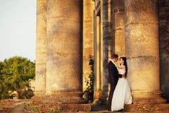 在户外婚礼礼服的美好的夫妇在专栏附近 库存图片