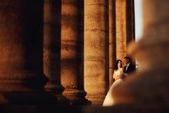 在户外婚礼礼服的美好的夫妇在专栏附近 库存照片