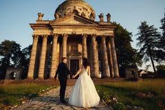 在户外婚礼礼服的美好的夫妇在古色古香的维多利亚女王时代的教会附近 图库摄影