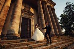 在户外婚礼礼服的美好的夫妇在城堡附近 图库摄影