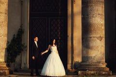 在户外婚礼礼服的美好的夫妇在城堡附近 免版税库存图片