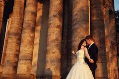 在户外婚礼礼服的美好的夫妇在城堡附近 免版税库存照片