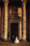 在户外婚礼礼服的美好的夫妇在老维多利亚女王时代的教会附近 免版税库存照片