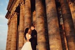 在户外婚礼礼服的美好的夫妇在老维多利亚女王时代的教会附近 图库摄影