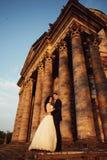 在户外婚礼礼服的美好的夫妇在维多利亚女王时代的教会附近 免版税库存照片