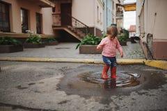 在户外水坑的女孩戏剧 库存图片
