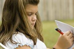 在户外纸张的女孩文字 免版税库存照片