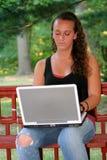 在户外膝上型计算机垂直后的青少年的女孩 免版税库存照片