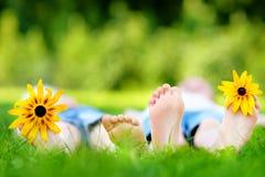 在户外草的两儿童英尺在夏天公园 免版税库存照片