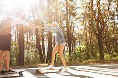 在户外滑板的爱恋的夫妇 在旁边查找 免版税库存照片