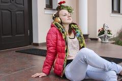 在房子前面的女孩听的音乐 免版税库存照片