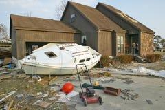 在房子前面的小船和残骸 免版税库存图片