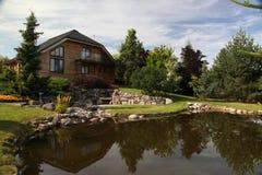在房子前面的庭院池塘 在一个大村庄的一个围场筑成池塘 库存照片