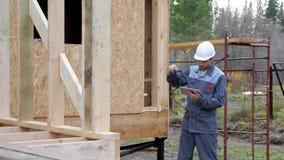 在房子前面的白种人工作者 建筑师或建造者检查在一个半建造的木构架房子里计划 在a的建造者 股票视频