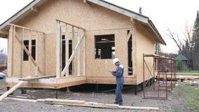 在房子前面的白种人工作者 建筑师或建造者检查在一个半建造的木构架房子里计划 在a的建造者 影视素材