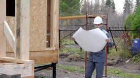 在房子前面的白种人工作者 建筑师或建造者检查在一个半建造的木构架房子里计划 在a的建造者 股票录像