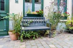 在房子前面的老和被风化的木长凳有花盆的 免版税库存照片