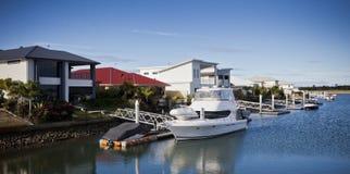 在房子前面靠码头的美丽的游艇 图库摄影