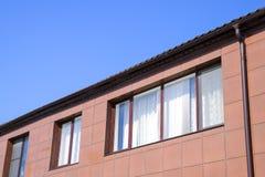 在房子和一个溢洪道系统的塑料窗口在屋顶 有塑料窗口和波纹状的板料一个棕色屋顶的议院  库存图片