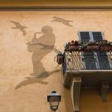 在房子墙壁上的艺术:Saxist和鸽子从网状电线 免版税库存照片