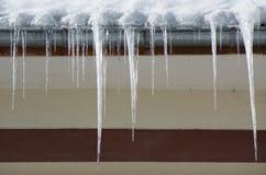 在房子屋顶的危险冰柱 库存照片