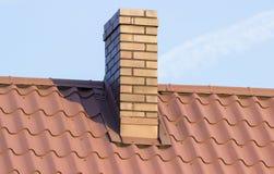 在房子屋顶的布朗烟囱在晴天 免版税库存照片