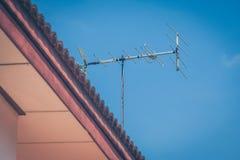 在房子屋顶的电视天线有蓝天背景 免版税库存图片