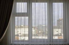 在房子屋顶的美丽的景色在从家庭窗口的晴朗的夏日 免版税库存照片