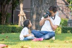 在房子庭院,家庭里生拍与女儿照相机的照片  免版税库存照片