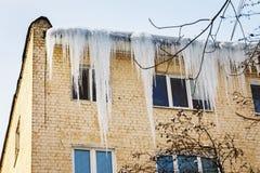 在房子房檐的危险冰柱  阻拦窗口和危及人的冰 库存照片