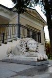 在房子沃龙佐夫前面的狮子雕象在公园Salgirka,辛菲罗波尔,乌克兰 图库摄影