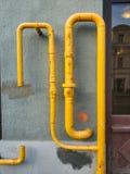 在房子的墙壁上的黄色管子 免版税库存照片