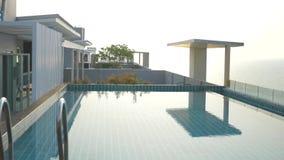 在房子的屋顶的一个豪华水池有海视图 在日落 4k,慢动作,在水的太阳强光 股票视频