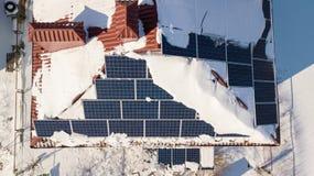 在房子的屋顶的太阳电池板在以后的大雪在冬天 可再造能源生产模块 免版税库存照片