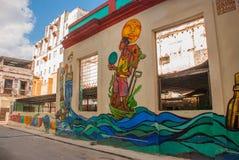 在房子的异常的街道画,画在墙壁上:下水道,水,人 哈瓦那 古巴 库存图片