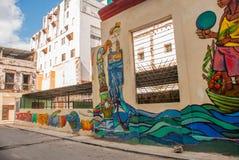 在房子的异常的街道画,画在墙壁上:下水道,水,人 哈瓦那 古巴 免版税库存照片