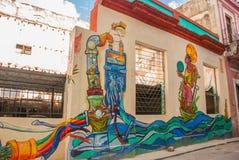 在房子的异常的街道画,画在墙壁上:下水道,水,人 哈瓦那 古巴 免版税图库摄影