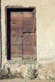 在房子的石墙上的老木门 免版税库存图片