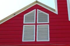在房子的红色背景的白色窗口 免版税库存图片