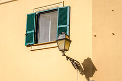 在房子的门面的金属灯笼葡萄酒减速火箭的街道照明有窗口的是闭合的快门和窗帘在一个晴天 免版税库存图片