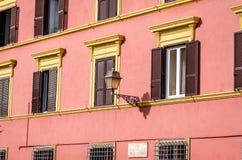 在房子的门面的金属灯笼葡萄酒减速火箭的街道照明有窗口的是闭合的快门和窗帘在一个晴天 库存照片