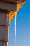 在房子角落的冰柱在清楚的天空 免版税库存照片