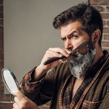 在房子里供以人员刮在卫生间里 理发店概念 髭蜡 发廊和理发师葡萄酒 库存图片