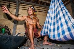 在房子里供以人员坐在与一个婴孩的摇篮附近的Mentawai部落 库存图片