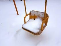 在房子附近的儿童操场在冬天-摇摆 库存照片